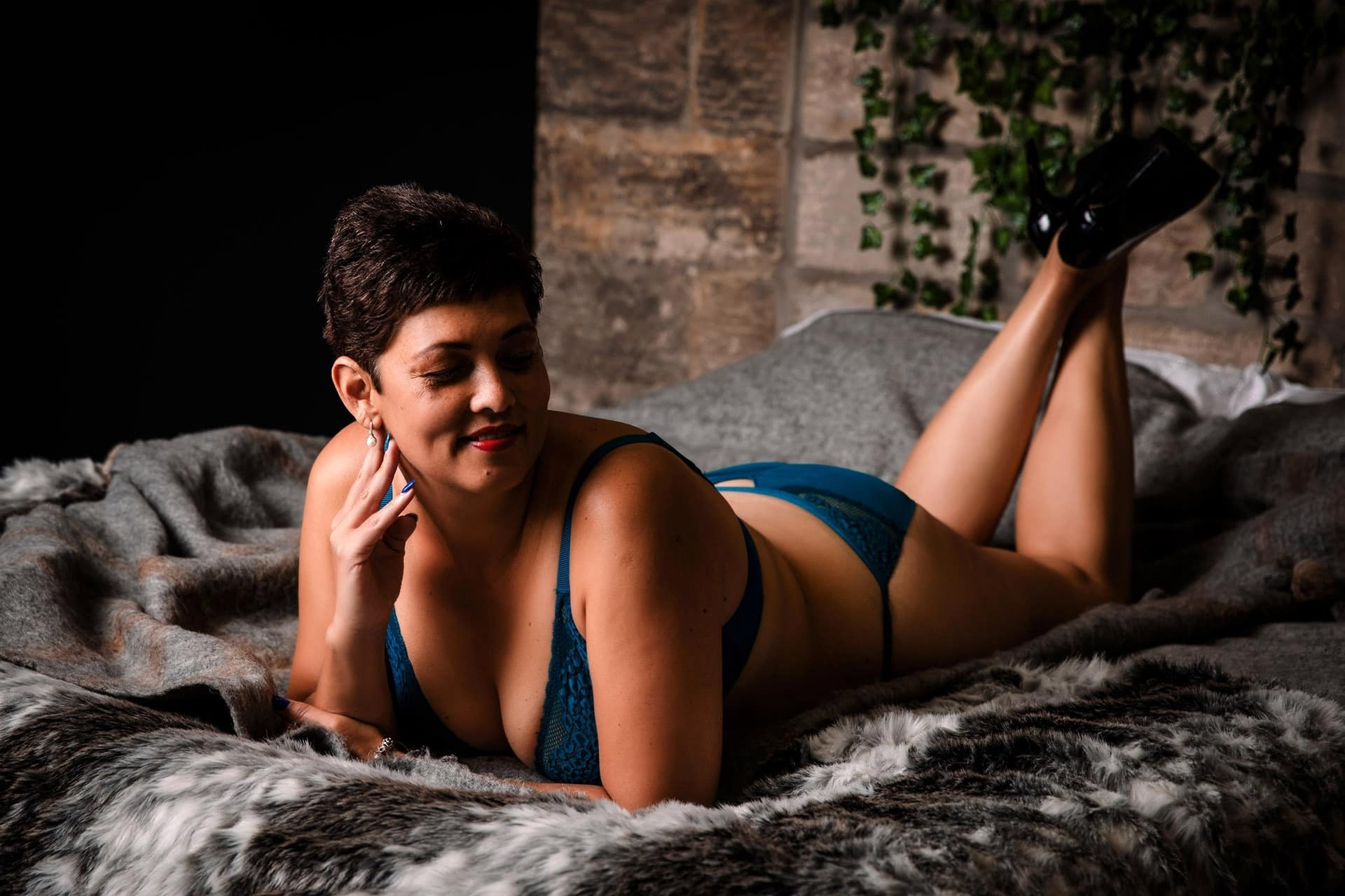 mature woman laying on bed for boudoir shoot